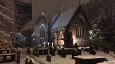 A snowy church and graveyard seen at night in Warrington, UK