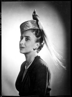 Small tilted pillbox hat with a bird of paradise on top. The model and milliner is the great Lilly Daché (1898-10-10 to 1989-12-31) . Photo by François Kollar. French Photographic Archive.