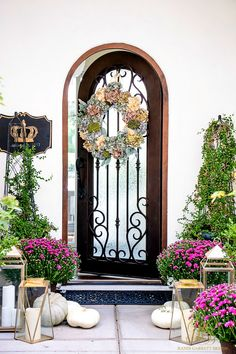 Autumn entryway with gold lanterns, white pumpkins, a blue hydrangea wreath, and purple mums. Fresh Ideas for Fall Home Tour - Elegant Fall Decor - Randi Garrett Design