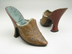 """Mules, England, c 1725-1750. Golden-brown leather embroidered in metal threads. Leather soles with 4"""" heels tapering at centre and widening to base, covered in red leather.  Manchester Art Gallery."""