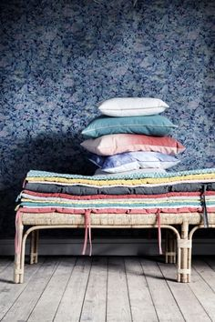 Cushions and blankets with floral wallpaper.