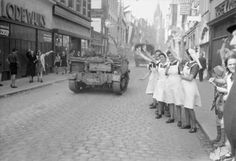 Dutch nurses wave at passing British vehicles during the liberation of Eindhoven, 19 September 1944.