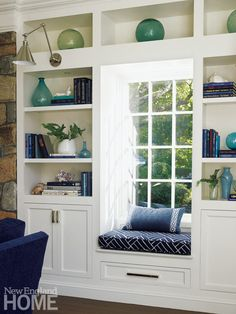 A cozy window seat surrounded by bookshelves featuring watery-colored glass accessories. Architecture: Louise Brooks, Brooks & Falotico Associates, Interior Design: Lynn Morgan, Lynn Morgan Design, Photography: Tria Giovan