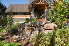 HGTV presents a front yard space featuring a rock garden with stream, waterfall, small wooden bridge, paver walkway and stone steps.