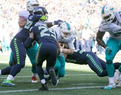 Miami Dolphins quarterback Ryan Tannehill scores a touchdown on a quarterback…