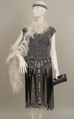 1920s black silk dance dress embroidered throughout with tiny glass beads and diamante on a fine black chiffon silk ground in Art Deco design with an original Art Deco evening purse to match, white feather boa, and diamante headband.