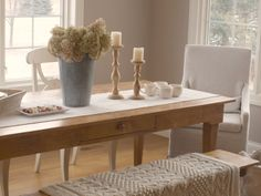 Minimal modern farmhouse dining room with country decor and European style/pine farmhouse table/linen runner/rustic wood candlesticks/galvanized vase with hydrangea/Rae Dunn dishes/pine dining bench/cableknit throw/Belgian linen dining chair (RH)/Hello Lovely Studio