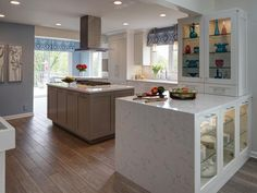 A peninsula with waterfall countertop helps separate the kitchen from the adjacent room. Glass cabinets at the end showcase the homeowner's colorful collection of Depression-era glass.