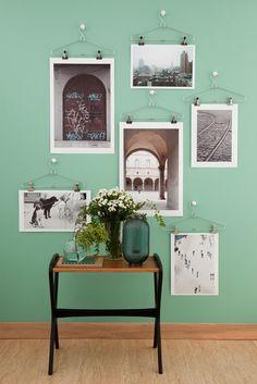 Expor fotos no cabide é a novidade. As lindas imagens clicadas pela fotógrafa Cacá Bratke ganham vida nova com estes arranjos de parede. Os cabides, usados como suporte, e a luminária são da Tok & Stok. Esta mesa é da Desmobilia.