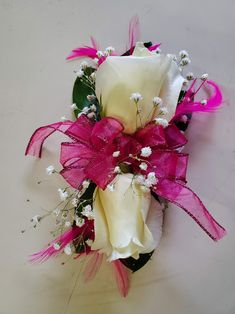 White roses, baby's breath, green leaves, pink bow with pink feathers on a wristlet. Crepe Paper Flowers, Pink Feathers, Wrist Corsage, Baby's Breath, Corsages, Boutonnieres, White Roses, Green Leaves, Gift Wrapping