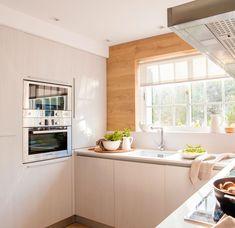 Zona de hornos y fregadero en cocina en tonos blancos con una gran ventana al exterior.
