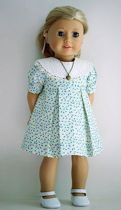 Vintage style dress w/ removable collar. Full front view. The cotton fabric has an eggshell background with tiny mint stems, buds, and capri blue leaves and tiny peach dots. Two box pleats in both front and back, empire waist, round collar, and fitted sleeves. The bodice is fully lined with batiste and the hem hand sewn.