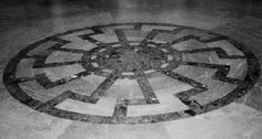 The photo above shows the dark green Sun Wheel emblem, or Sonnenrad in German, on the gray-blue marble floor of the SS Generals hall inside the North tower at Wewelsburg castle. Description from scrapbookpages.com. I searched for this on bing.com/images