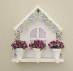 Porta chaves super charmoso e delicado para decorar sua casa e organizar suas chaves! Casinha porta chaves em mdf com 3 pinos em madeira e flores vazadas nas laterais. Na cor branca com detalhes nas cores verde e lilás. Com cortina (tecido na parte de trás) na cor lilás. Com 3 mini vasinhos em cerâmica branca com arranjos de mini rosas de tecido. Envernizada. Medidas: 21cm de altura x 18,5cm de comprimento R$ 63,00