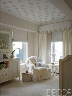 The nursery's armchair and dresser are by  Restoration Hardware Baby & Child, the mohair throw is by Susan Chalom, available to the trade from Holly Hunt, the mirror is by Marc Bankowsky, the chandelier is of Murano glass, and the ceiling is covered in a Sandberg wallpaper.