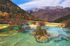 Huanglong, Cina . Huanglong è un'area che si trova nella Contea di Songpan, nella  provincia di Sichuan, in Cina.  Questa zona è famosa per i numerosi laghetti formati da depositi di  calcite, per gli ecosistemi delle sue foreste, per i picchi innevati e  le cascate che punteggiano il territorio. Qui si trovano numerose specie  in pericolo d'estinzione, fra cui il panda gigante. Nel 1992 Huanglong fu inserita nell'elenco dei Patrimoni dell'umanità  dell'Unesco
