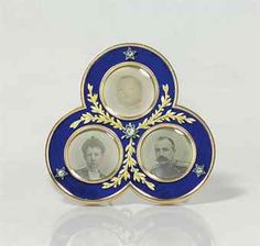 A JEWELED TWO-COLOR GOLD, SILVER AND GUILLOCHÉ ENAMEL PHOTOGRAPH FRAME BY FABERGÉ, WORKMASTER VIKTOR AARNE, ST. PETERSBURG, CIRCA 1901. Trefoil, enameled in translucent royal blue over a wavy guilloché ground, with three oval apertures enclosing photographs of Grand Duke George Mikhailovich, Grand Duchess Marie, and Princess Nina Georgievna, applied with gold laurel vines and diamond set stars, with mother of pearl back and silver-gilt scroll strut, the back inscribed 'X-Mas-1901'/G. M. N.'