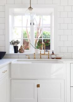Lovely kitchen features white shaker cabinets adorned with antique brass vintage latch hardware ...