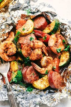 Cajun Shrimp and Sausage Vegetable Foil Packets These foil packets are loaded with shrimp, sausage, summer vegetables and tossed in cajun spices. Quick and easy and packed with big flavor! Shrimp Foil Packets Oven, Shrimp Boil Foil, Foil Packet Dinners, Foil Pack Meals, Tin Foil Dinners, Grilled Foil Packets, Salmon Foil Packets, Garlic Shrimp, Pastas Recipes