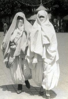 Two veiled Algerian women wearing chalwars. Algiers, 1932.