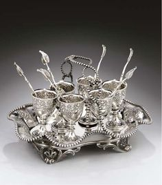 A VICTORIAN SILVER SIX-CUP EGG CRUET, MARK OF ROBERT HENNELL, LONDON, THE STAND 1856, THE CUPS 1855, SHAPED OBLONG WITH BEAD BORDERS & BEADED MULTIPLE LOOP HANDLE, ON OPENWORK FOLIATE SCROLL FEET, SIDES CHASED WITH FOLIATE SCROLLWORK PANELS & STRAPWORK, THE CUPS FURTHER DECORATED WITH SATYR MASKS, TOGETHER WITH 6 SPOONS WITH LEAF BOWLS & TERMINALS BY SEBASTIAN CRESPEL, LONDON, 1849