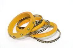 Juego de pulseras de aro amarillas: 3 de madera con tachuelas y 4 de metal dorado envejecido labradas    Medidas diámetro 7 cm  Ref.: Ag7450Y  http://www.meigallo.com/articulo/708/set-de-pulseras-rigidas