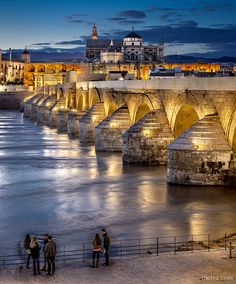 HISPANIA ROMANA Roman Bridge on Guadalquivir river and Mezquita Cathedral at twilight in Cordoba, Spain.  The bridge was built by the Romans in the early 1st century BC, perhaps replacing a previous wooden one.The Via Augusta, which connected Rome to Cádiz, most likely passed through it.   Construido a principios del siglo I d.C., durante la época de dominación romana en Córdoba, sobre el río Guadalquivir. Probablemente la Vía Augusta que iba desde Roma hasta Cádiz pasaba por él.