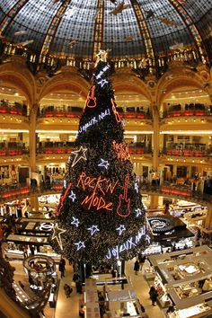 A giant decorated Christmas tree stands on the ground floor of Galeries Lafayette department store as people shop for gifts during the holiday season in Paris November 17, 2011.