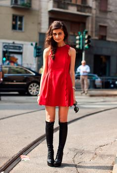 Natalia Alaverdian in a scalloped coral minidress and black laced boots