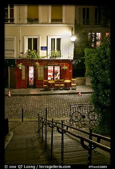 Hillside stairs on butte, street and Chez Marie restaurant at night, Montmartre. Paris, France