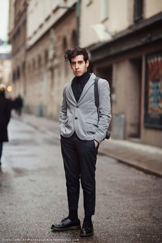 Kristian David in a gray cotton blazer, black shirt with flower pins, trousers, and DOC MARTENS.