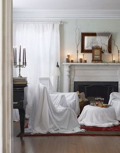 """Eerie living room: Use sheet-draped chairs to give your room the look of ruin. Then, string a cheesecloth """"cobweb"""" across a mirror and secure curly willow branches in candlesticks with museum wax.    #halloween #decorating"""