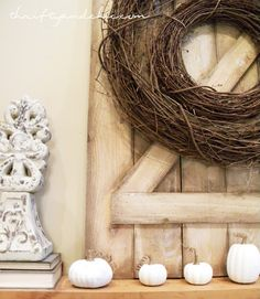 Small barn door used on a mantle as a backdrop for a wreath and some fall decor!
