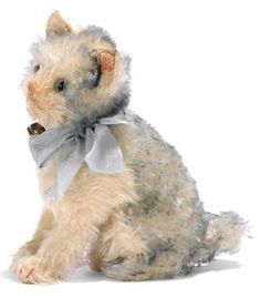 A STEIFF HEAD-TURNING FLUFFY, (3323,2H), seated, grey tipped mohair, green and black glass eyes, pink stitching, whisker, red stitched claws, tail-operated head mechanism, ribbon with bell and FF button with red cloth tag, circa 1932 --7½in. (18.5cm.) high (red tag worn)