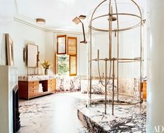 The master bath is clad in dramatically figured Paonazzo marble; the freestanding shower was designed by Dirk Denison.