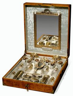Silver-gilt nécessaire de voyage in the Louis XVI style, each piece engraved with monogram NM within an escutcheon below a marquis' coronet, comprising a table mirror, a pair of three-light candelabra, three pairs of cut-glass perfume flagons with silver-gilt caps, three hair brushes, a pin box, and a pair of rectangular cloth brushes, in original fitted oak case, circa 1890.