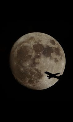 plane silhouette with moon on black