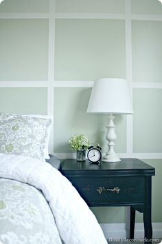 Love the all white lamp with colored bed side table and pattern of bedding.