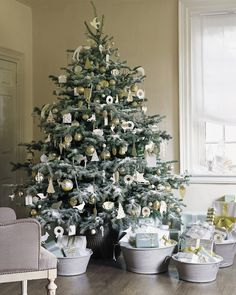 A Christmas tree dusted with snow looks even frostier when decorated exclusively in shades of silver, white, and cream. Simple paper-and-glitter ornaments mix well with vintage metallic pieces. Glitter ornaments are easy to make and can be saved from year to year.