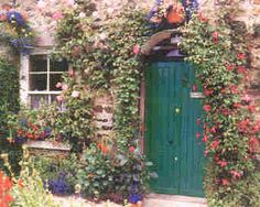 Roses surround the green door and wall on this English cottage.