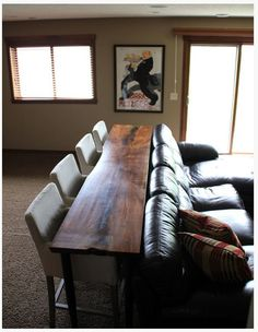 Great idea for extra seating in basement. Table/bar behind couch with stools or chairs instead of the usual bar.