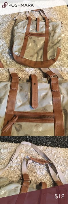 American Eagle Outfitters cross body bag Cream bag with silver polka dots and tan leather like accents. Has shoulder straps and an adjustable cross body strap. There's a strap with two closure holes that closes the bag together. Minimal pockets inside. American Eagle Outfitters Bags Crossbody Bags