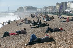 SOAKING IT IN: People lay on a beach in Brighton, England, Sunday. (Stephen Lock/I-Images/Zuma Press)