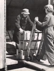 Second World War porters Miss Gaygill and Mrs Hodgkins load goods onto a train.    Photographed by Topical Press, 30 Apr 1942