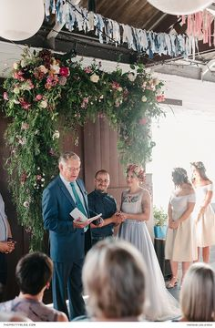 An eye-catching installation of greenery, jazzed up with bright flowers, adorned this creative couple's ceremony space. | Photographer: Liesl le Roux Photography | Florist: Holloway Floral Design | Wedding Dress Designer: FashionCollective