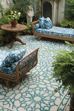 Beautiful patterned outdoor rug paired with wicker chaise lounges and blue and white patterned upholstery.