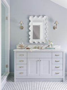Gray bathroom features sloped ceiling over cool gray walls framing Ballard Designs Atoll Mirror flanked by Ralph Lauren Anette Single Sconces in Polished Nickel situated over light gray washstand topped with white marble atop marble basketweave floor next to walk-in shower.