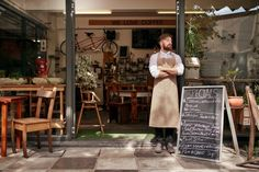 Barista standing in the doorway of a restaurant by jacoblund. Portrait of young man standing at the entrance of his coffee shop with a black board. Barista standing in the doorway. Design Food, Design Café, Design Garage, Shop Front Design, Shop House Plans, Shop Plans, Best Business To Start, Successful Business, Coffee Shop Business
