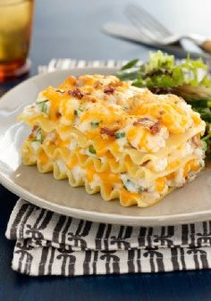 """Easy """"Pierogi"""" Casserole – 9  lasagna noodles; 4 cups hot mashed potatoes; 1/2 cup Chive & Onion Cream Cheese Spread; 1 pkg. (3oz.) Bacon Bits; 2 cups Shredded Triple Cheddar Cheese"""