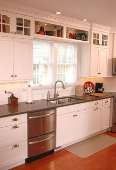Renovated galley kitchen with shaker-style cabinets in the work area. By Neal's Design Remodel.